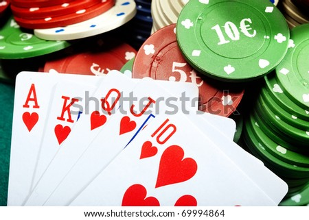 Royal flush and poker chips on a green table of casino - stock photo