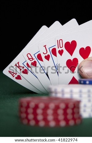 Royal Flush in focus with red, white and blue poker chips on a green felt surface.