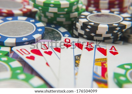 Royal flush poker hand with poker chips stack - stock photo