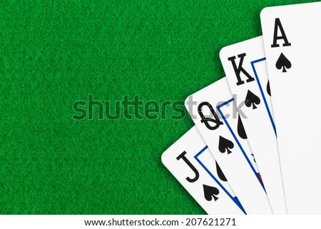 Royal flush poker playing cards on green felt background - stock photo