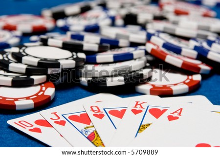 Royal flush with a pot of chips behind - stock photo