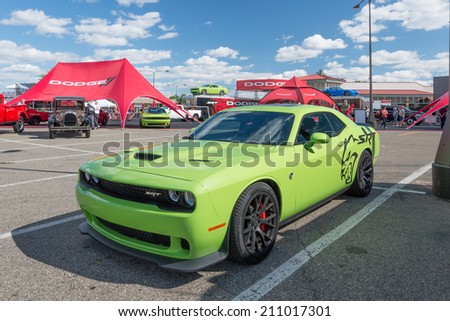 ROYAL OAK, MI/USA - AUGUST 14, 2014: A 2015 Dodge Challenger SRT Hemi Hellcat car, two Dodge Challengers, and a Viper at the Woodward Dream Cruise, the world's largest one-day automotive event.  - stock photo