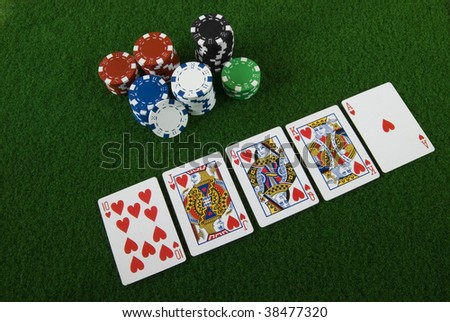 Royal straight flush and some poker chips - stock photo