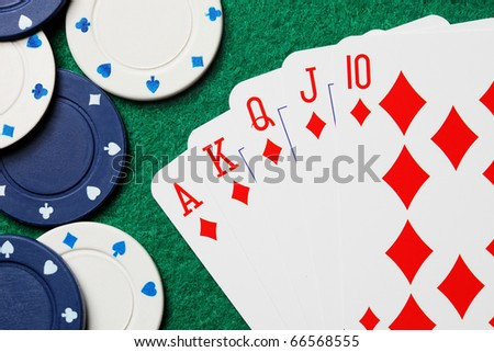 Royal straight flush poker cards with gambling chips on a green felt table background - stock photo