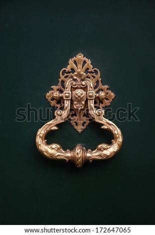 Royal style doorknocker on green door. - stock photo