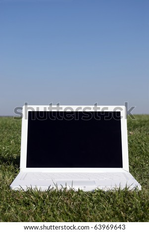 Royalty Free Stock Image of a photograph of a laptop on grass against a clear blue sky providing copy space above in a conceptual manner