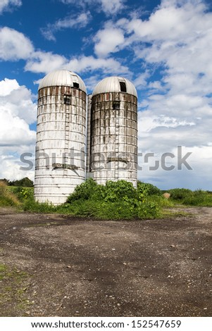 Royalty-free stock image of two old farm silos on an over grown farm in Vermont on a summer day. - stock photo