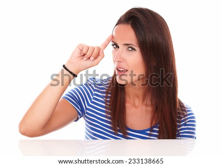 Rreflective young woman wondering while pointing to her forehead on white background - stock photo