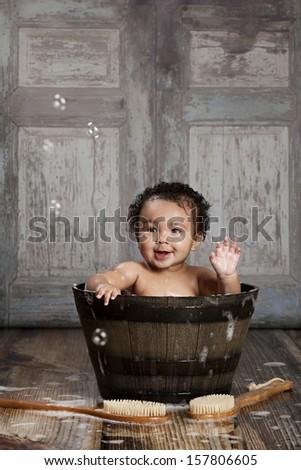 Rub-a-dub-dub!  Adorable baby boy in a wooden tub. - stock photo