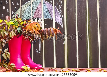 Rubber boots (rainboots) and autumnal leaves are on the wooden fence background with drawing umbrella and rain drops. Autumn. Copy space for text. Creative, activity, leisure, travel concept.  - stock photo
