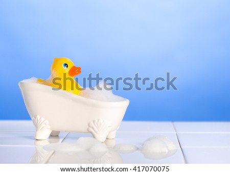 Rubber duck in the bath with soap suds on a blue background - stock photo
