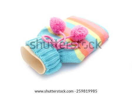 rubber hot water bottle in a knitted colorful cover color isolated on white background - stock photo