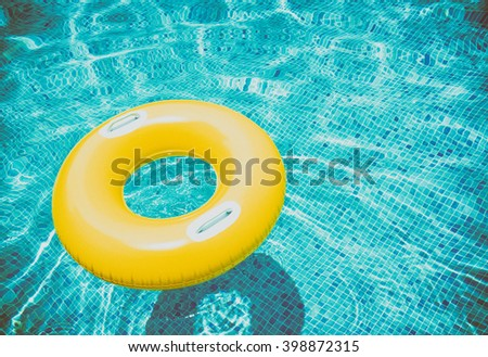 rubber ring floating in transparent blue pool, retro toned - stock photo