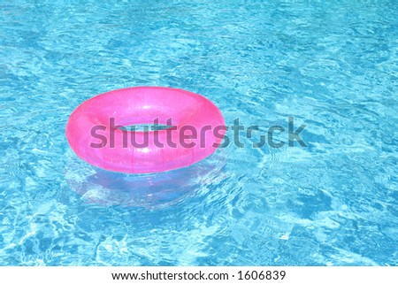 rubber ring in blue pool - stock photo