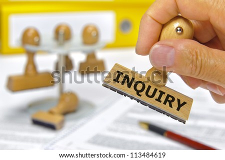 rubber stamp in hand marked with inquiry - stock photo