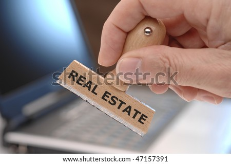 rubber stamp with inscription: REAL ESTATE - stock photo