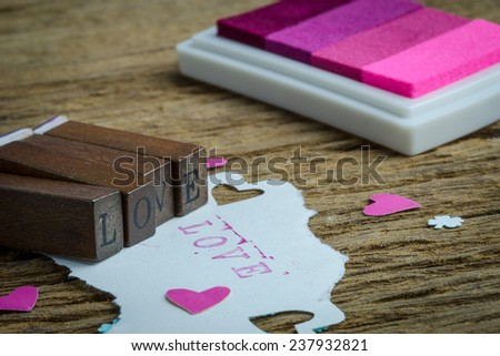 Rubber stamp with letters L O V E with ink pad on wooden table - stock photo