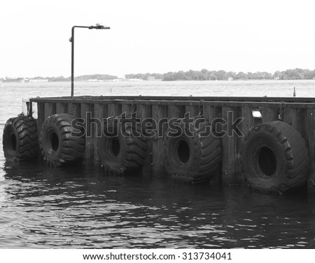 Rubber tire lined pier or wharf for docking boats or ships on lake Ontario. - stock photo
