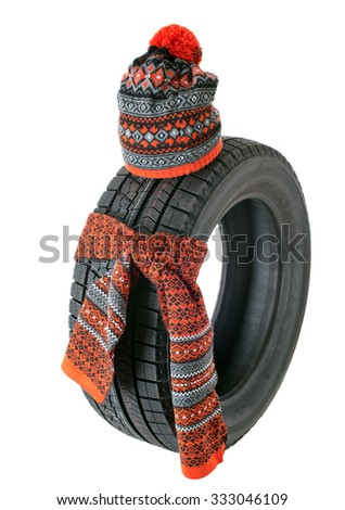 Rubber tire with a knotted scarf and winter hat. Isolated. - stock photo