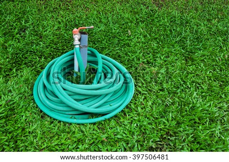 Rubber tube for watering plants in the garden,Rubber tube on grass in the garden - stock photo