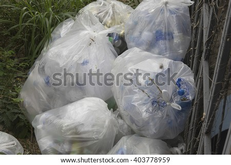 rubbish bag Trash plastic beside the fence - stock photo
