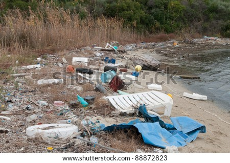 Rubbish washed up on a small beach - stock photo