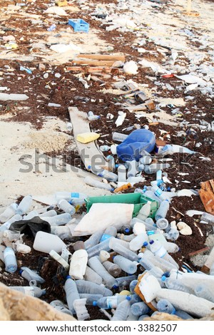 Rubbish washed up on the shore in the Arabian Gulf. Mineral water bottles, shampoo bottles and old tins are among the hazards facing marine wildlife despite regulations controlling dumping. - stock photo