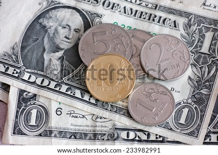 Ruble coins on dollar banknotes. - stock photo