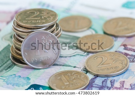 rubles coins against background of 1000 and 500 rubles banknotes