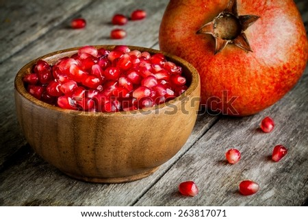 ruby pomegranate grains in a wooden bowl on a rustic table - stock photo