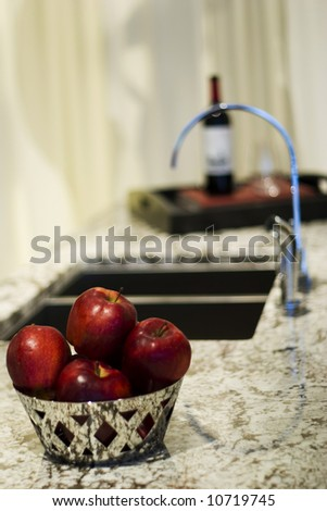 ruby red apples in basket in ultra modern kitchen - stock photo