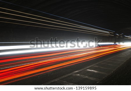 ruck light trails in tunnel. Art image . Long exposure photo taken in a tunnel - stock photo