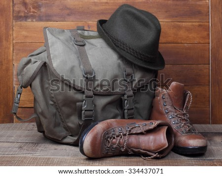 Rucksack with old boots and hat on wooden background. - stock photo
