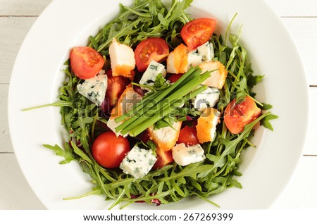 Rucola salad, tomato, mildew cheese, chive and fried chicken - stock photo