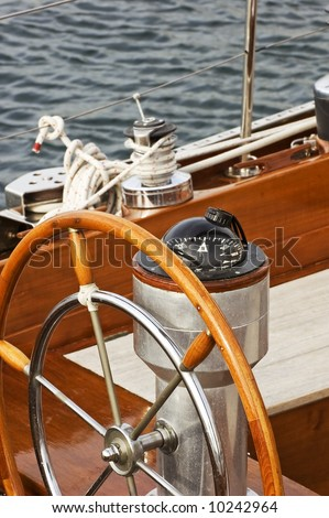 Rudder and compass on a wooden boat - stock photo