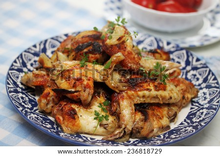 Ruddy baked chicken wings on a plate - stock photo