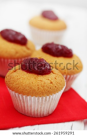 Ruddy muffins with berry cranberry jam on the table - stock photo