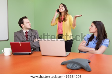 Rude colleague disturbing meeting by talking on Smartphone - stock photo