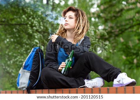 Rude girl smoking marijuana and drinking beer out of school - stock photo