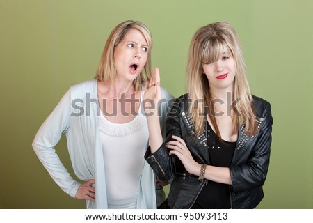 Rude retro-styled daughter gestures angry mom to be silent - stock photo