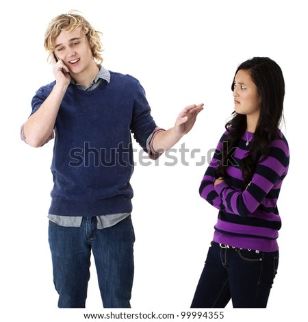 Rude young man on his cell phone puts up his hand to quiet his angry girlfriend - stock photo