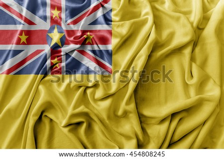 Ruffled waving Niue flag - stock photo