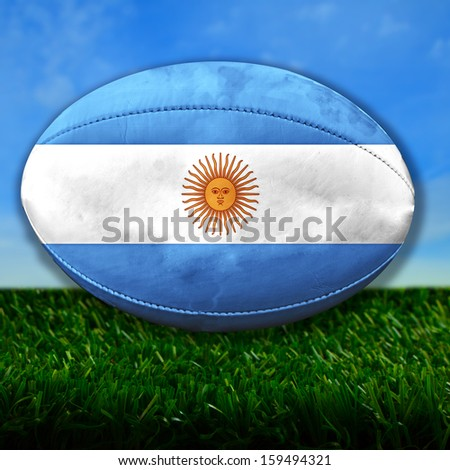 Rugby ball with Argentina flag over grass - stock photo