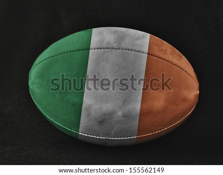 Rugby ball with Ireland flag colors, over black background - stock photo