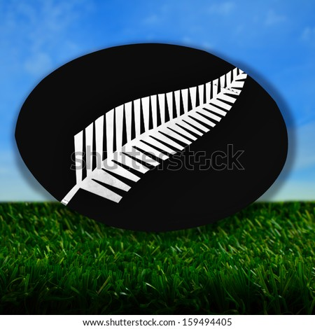 Rugby ball with New Zealand uniform colors, with silver fern, over grass - stock photo
