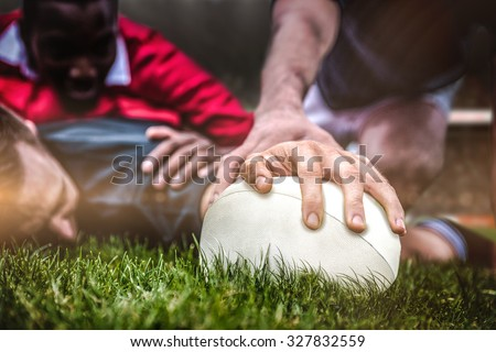Rugby fans in arena against rugby player scoring a try - stock photo