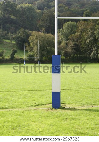 Rugby field with padded goal posts - stock photo