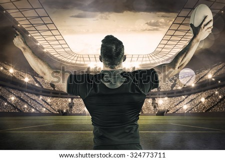 Rugby player celebrating with the ball against large football stadium with lights - stock photo