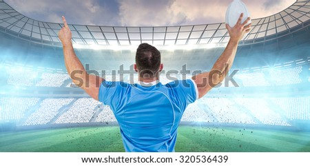 Rugby player cheering with the ball against rugby stadium