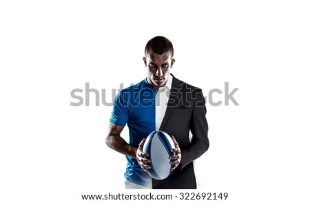 Rugby player holding ball against half a suit - stock photo